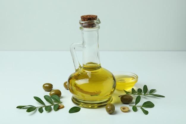 Fles en kom met olie, olijven en twijgen op wit oppervlak