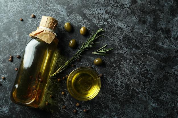 Fles en kom met olijfolie en kruiden op zwarte smokey-oppervlak