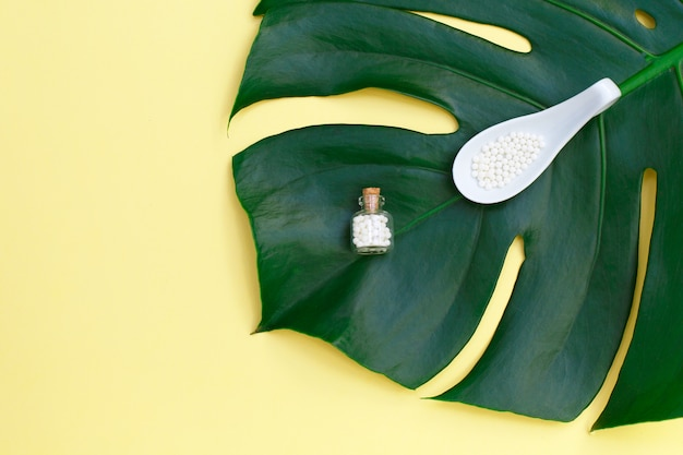 Fles en lepel met homeopathische pillen op palmblad.