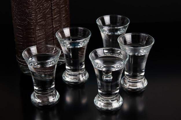 Fles en schot van wodka op een zwarte lijst