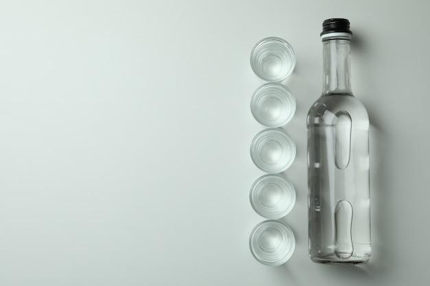 Fles en schoten van drank op witte muur