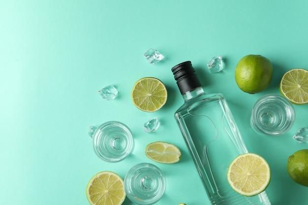 Fles en shots van drank, limoenen en ijs op muntmuur, bovenaanzicht