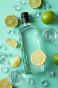 Fles en shots van wodka, limoenen en ijs op muntoppervlak, bovenaanzicht