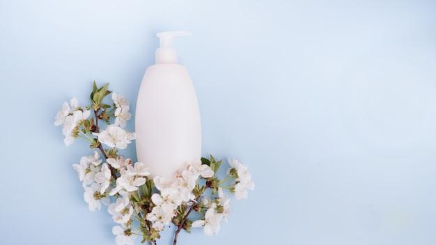 Fles en witte bloemen op blauwe achtergrond.