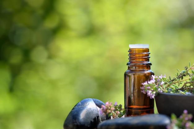 Fles etherische olie en bloemen van aromatische kruiden