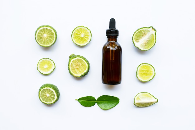 Fles etherische olie en verse kaffirkalk of bergamotfruit dat op wit wordt geïsoleerd.