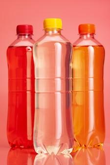 Fles gekleurde drank of limonade op een heldere roze achtergrond dicht omhoog