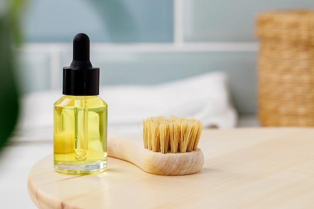 Fles gele cosmetische olie op houten dienblad close-up foto