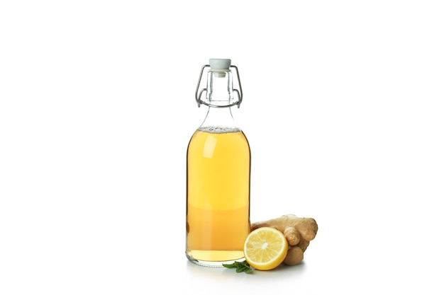 Fles gemberbier en ingrediënt op wit wordt geïsoleerd dat