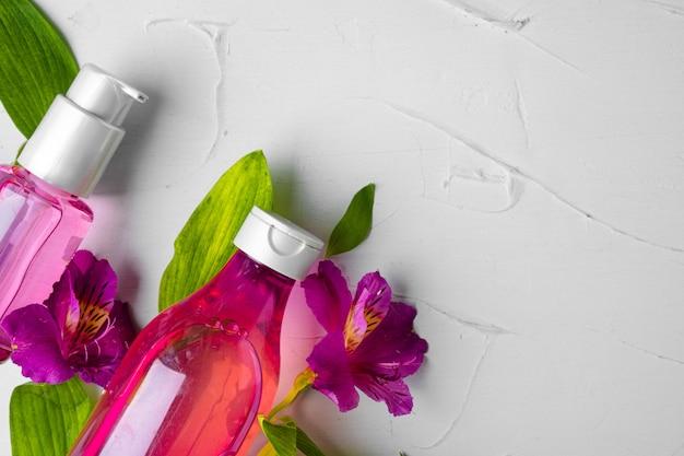 Fles geur of aromatische olie in een bos verse bloemen