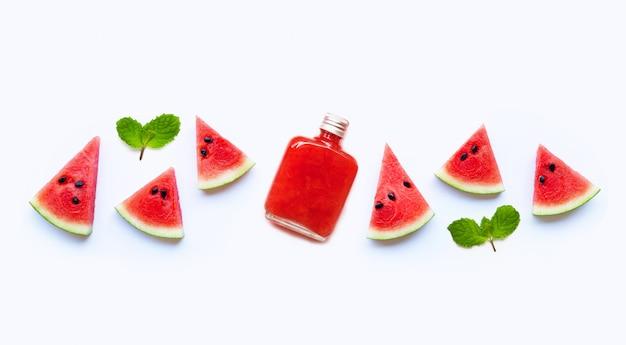 Fles gezond die watermeloensap met plak en muntbladeren op een wit worden geïsoleerd