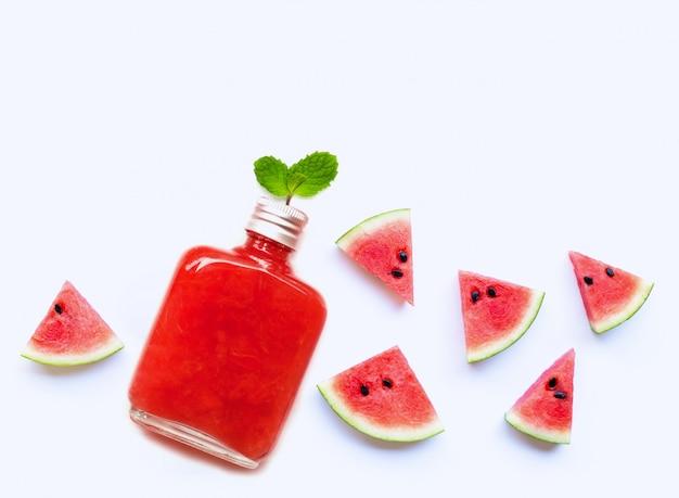 Fles gezond die watermeloensap met plak en muntbladeren op wit worden geïsoleerd