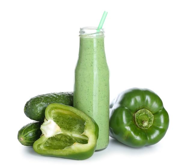 Fles gezonde smoothie met komkommer en paprika op witte ondergrond