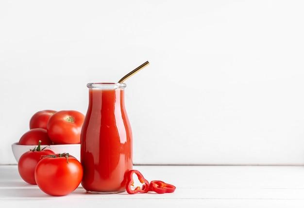 Fles gezonde smoothie met tomaat en paprika op lichte ondergrond