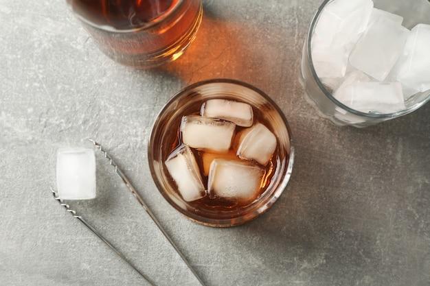 Fles, glazen met ijsblokjes en whisky op grijze achtergrond, bovenaanzicht