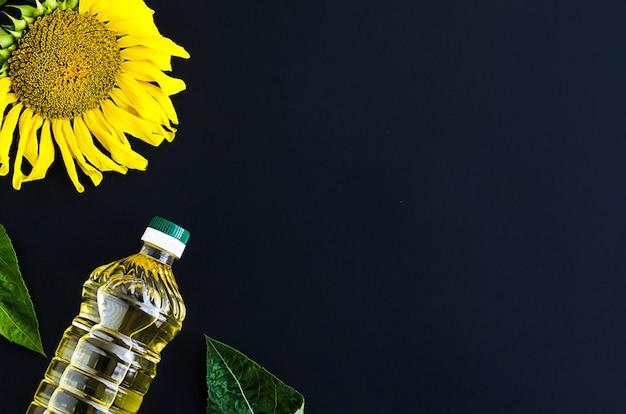 Fles gouden zonnebloemolie en gele bloem op donkere zwarte achtergrond.