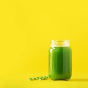Fles groene selderie smoothie op gele achtergrond