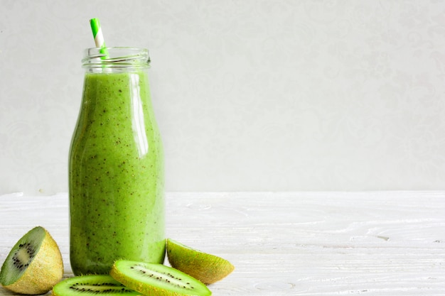 Fles groene smoothie met verse kiwi en banaan fruit en bessen