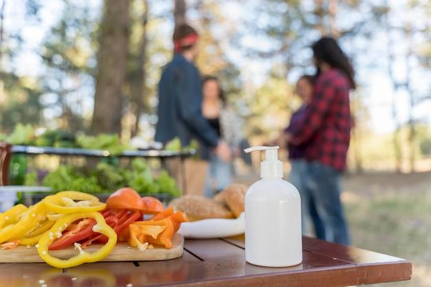 Fles handdesinfecterend middel op tafel terwijl vrienden een barbecue hebben