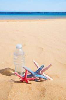 Fles helder koud water met zeester op zandstrand