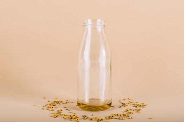 Fles honing met bijenstuifmeel op perzik gekleurde achtergrond