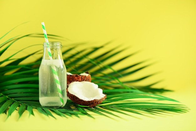 Fles kokoswater en vers rijp fruit. zomer eten concept. vegetarisch, veganistisch, detoxdrankje. kokosnotensap met stro op palmbladen