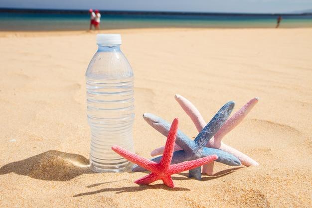 Fles koud water met zeesterren op zandstrand