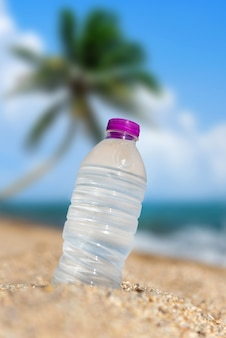 Fles koud zoet water op strandzand met palm. zomer concept