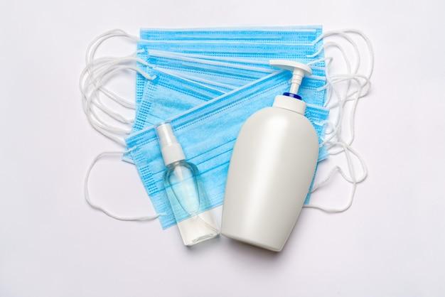 Fles lotion, ontsmettingsmiddel of vloeibare zeep en medisch beschermend masker dat op witte muur met het knippen van weg wordt geïsoleerd.
