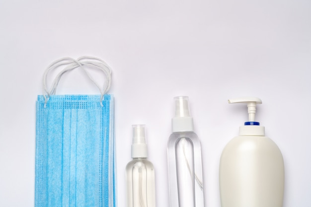 Fles lotion, ontsmettingsmiddel of vloeibare zeep en medische beschermend masker geïsoleerd op lichtgrijze muur.
