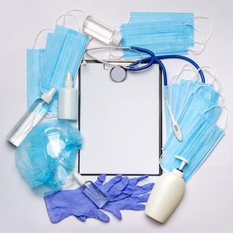 Fles lotion, ontsmettingsmiddel of vloeibare zeep, latex rubberen handschoenen, hoed, medisch masker, pillen, thermometer en veiligheidsbril op lichtgrijze achtergrond - platte lay-out