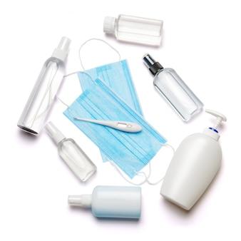 Fles lotion, ontsmettingsmiddel of vloeibare zeep, thermometer en medisch beschermend masker dat op witte muur met het knippen van weg wordt geïsoleerd