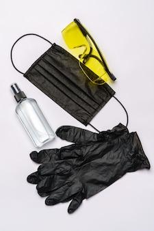Fles lotion, ontsmettingsmiddel of vloeibare zeep, veiligheidsbrilglazen en beschermend masker dat op witte muur met het knippen van weg wordt geïsoleerd.