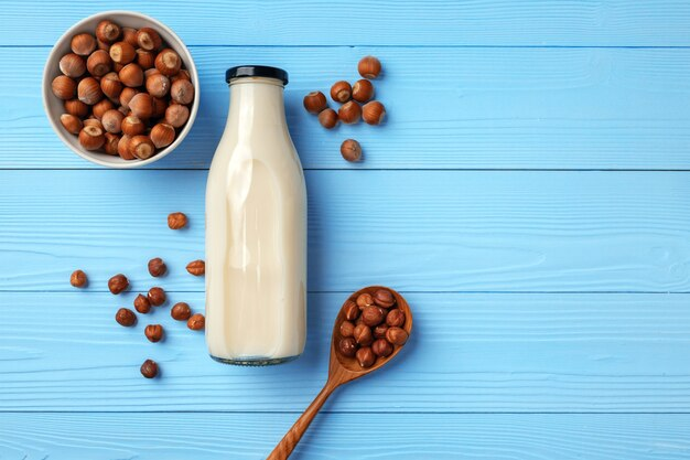 Fles melk en hazelnoten op houten achtergrond