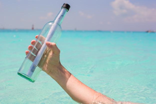 Fles met een bericht in de hand blauwe hemel als achtergrond