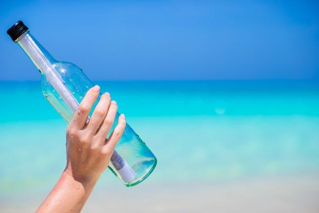 Fles met een bericht in de hand op blauwe hemel