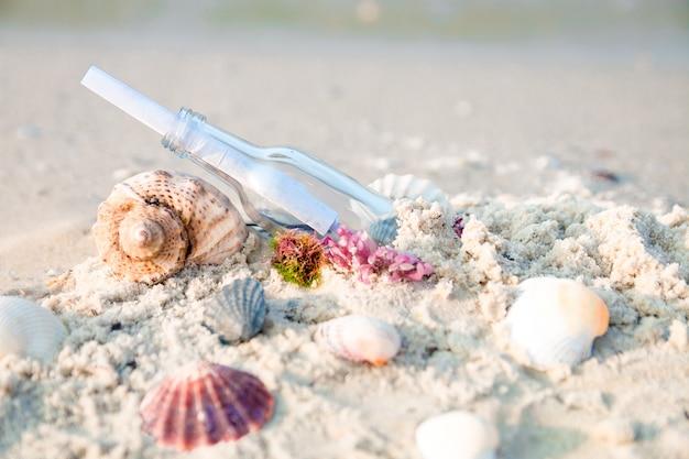 Fles met een bericht of brief op het strand dichtbij zeeschelp. sos