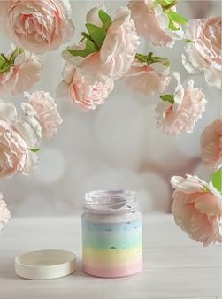 Fles met een veelkleurig romig cosmetisch product omringd door zwevende zachtroze pioenrozen.