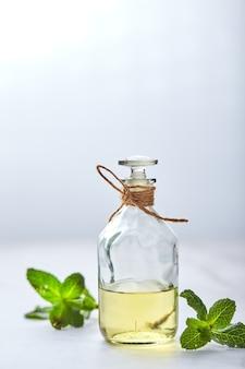 Fles met essentiële muntolie en groene blad natuurlijke biologische ingrediënten voor cosmetica huidverzorging lichaamsbehandeling schoonheidsverzorging concept