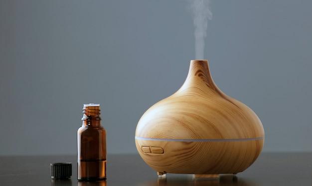 Fles met etherische olie met een elektrische ultrasone luchtbevochtiger die vernevelde waterdruppels afgeeft