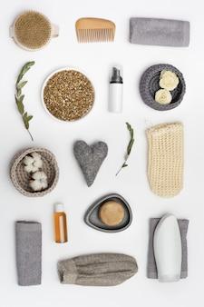 Fles met gelzeep, haarborstel, washandje, tak van eucalyptus op witte tafel