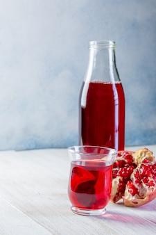 Fles met granaatappelsap en een glas, rijpe granaatappel, geheel en geschild op een witte houten achtergrond