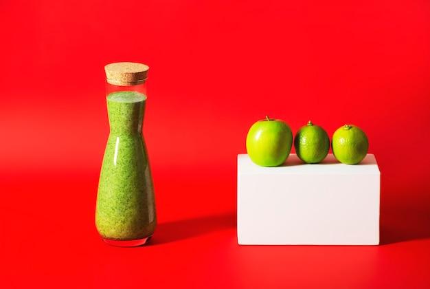 Fles met groene smoothie, ernaast een wit geometrisch prisma met appel en limoenen.