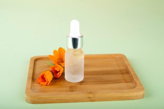 Fles met hyaluronzuur en oranje bloemen. schoonheid, cosmetica voor gezichtsverzorging voor persoonlijke verzorging.