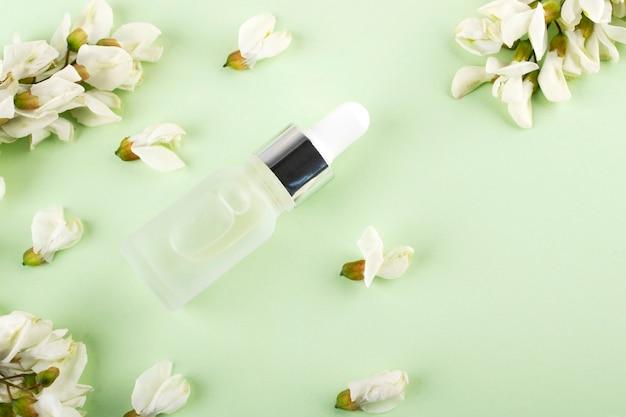 Fles met hyaluronzuur en witte bloemen. schoonheid, cosmetica voor gezichtsverzorging voor persoonlijke verzorging.