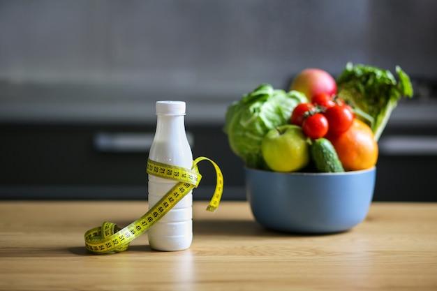 Fles met meetlint en seizoensgroenten en fruit in een kom