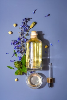 Fles met natuurlijke cosmetische aroma-olie en pipet op blauw oppervlak in bloemen