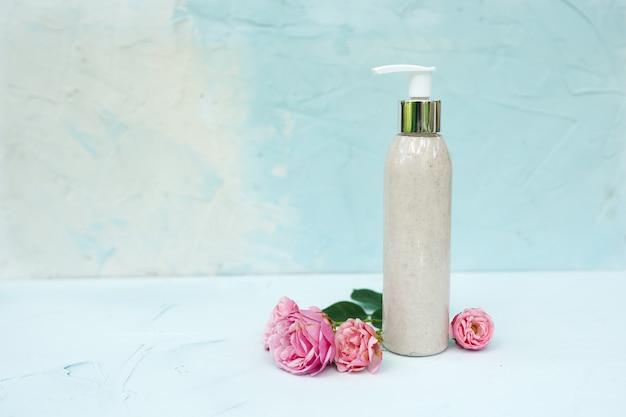 Fles met natuurlijke scrub en roze bloemen op pastel blauwe gestructureerde achtergrond. huidverzorging cosmetica, beauty spa-concept.