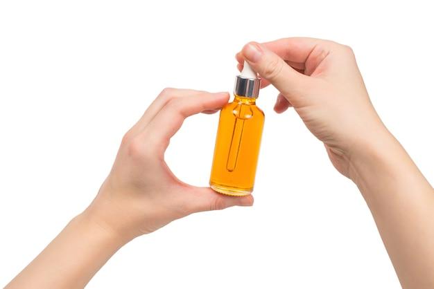 Fles met olie in vrouwenhand op wit wordt geïsoleerd dat. kopieer ruimte.