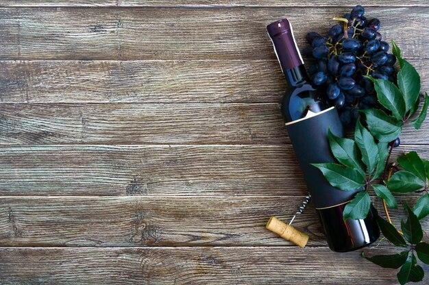 Fles met rode wijn, kurkentrekker, blauwe druiven, bladeren op een houten tafel.